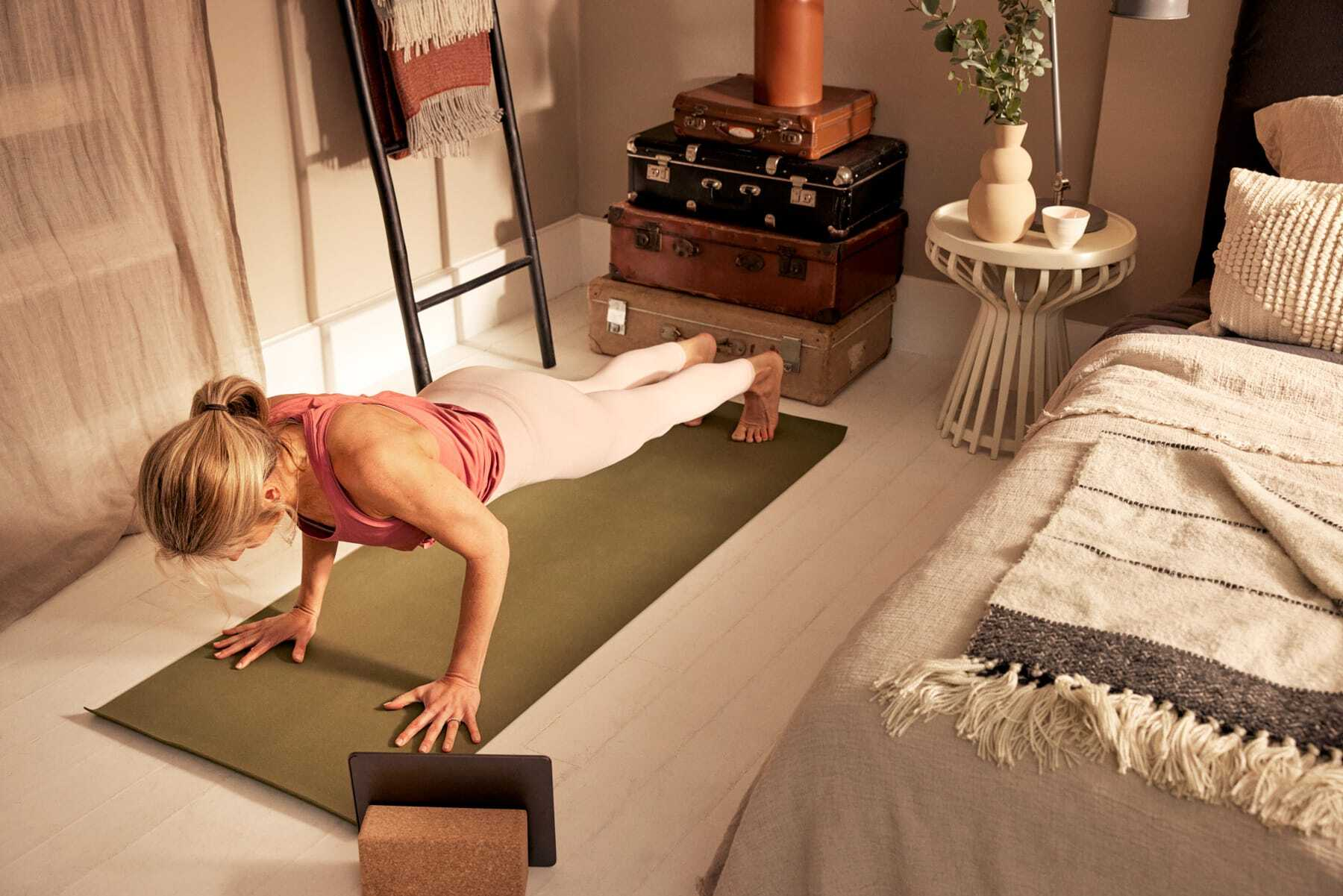 A woman facing downwards stretching on a pilates mat in her bedroom