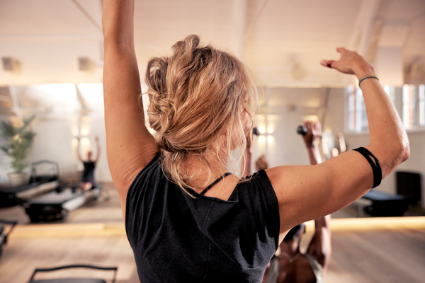 A woman in black gym clothes practising pilates seen from behind