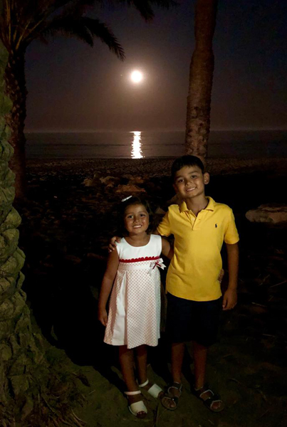 Children under moon on beach at night