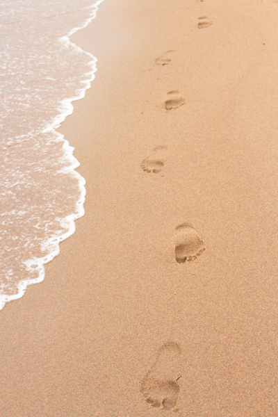 Footprints in the sand next to the sea