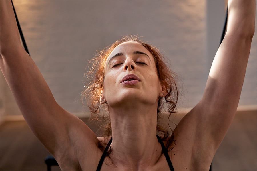 A woman practising pilates and breathing deeply