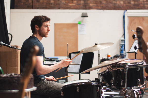 A man playing the drums in a studio