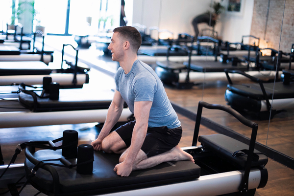 A man on a bench in a pilates studio