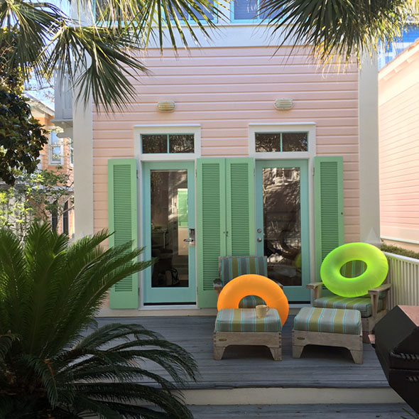 pink beach house with green shutters