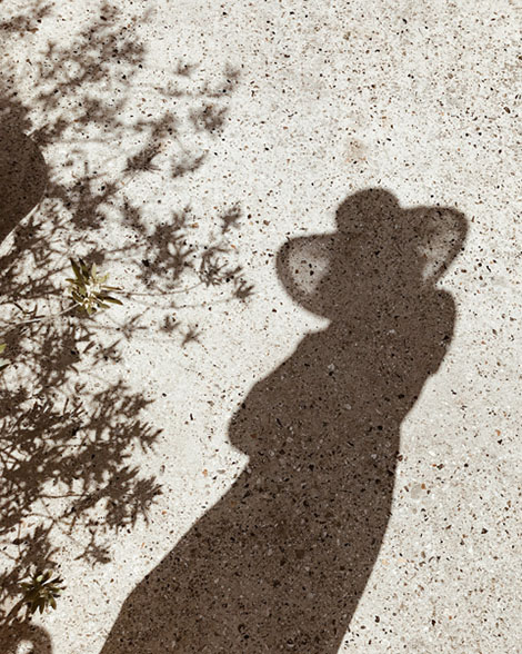 Woman in hat shadow on ground