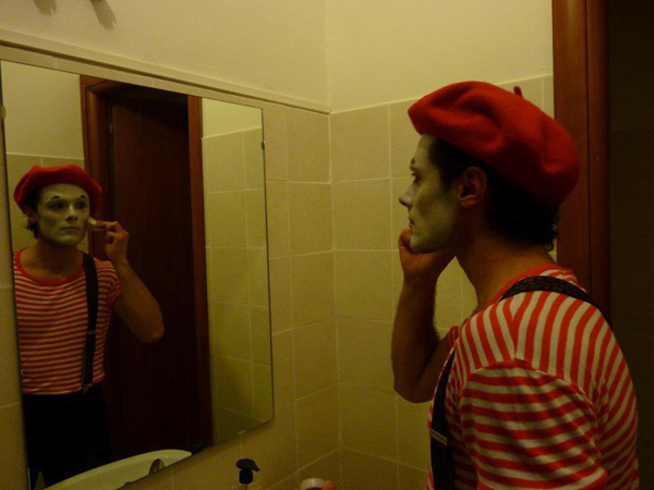 Clown putting on makeup in mirror