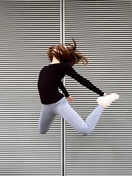 Woman jumping in front of grey wall