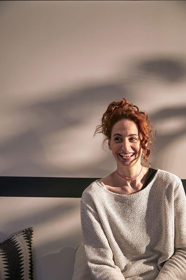 Georgina Koutsaimani laughing in a grey jumper