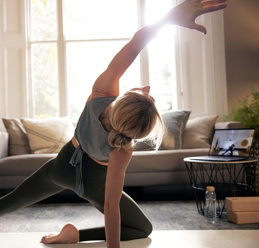 Woman exercising on laptop at home