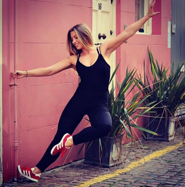 Woman doing dance move against pink wall