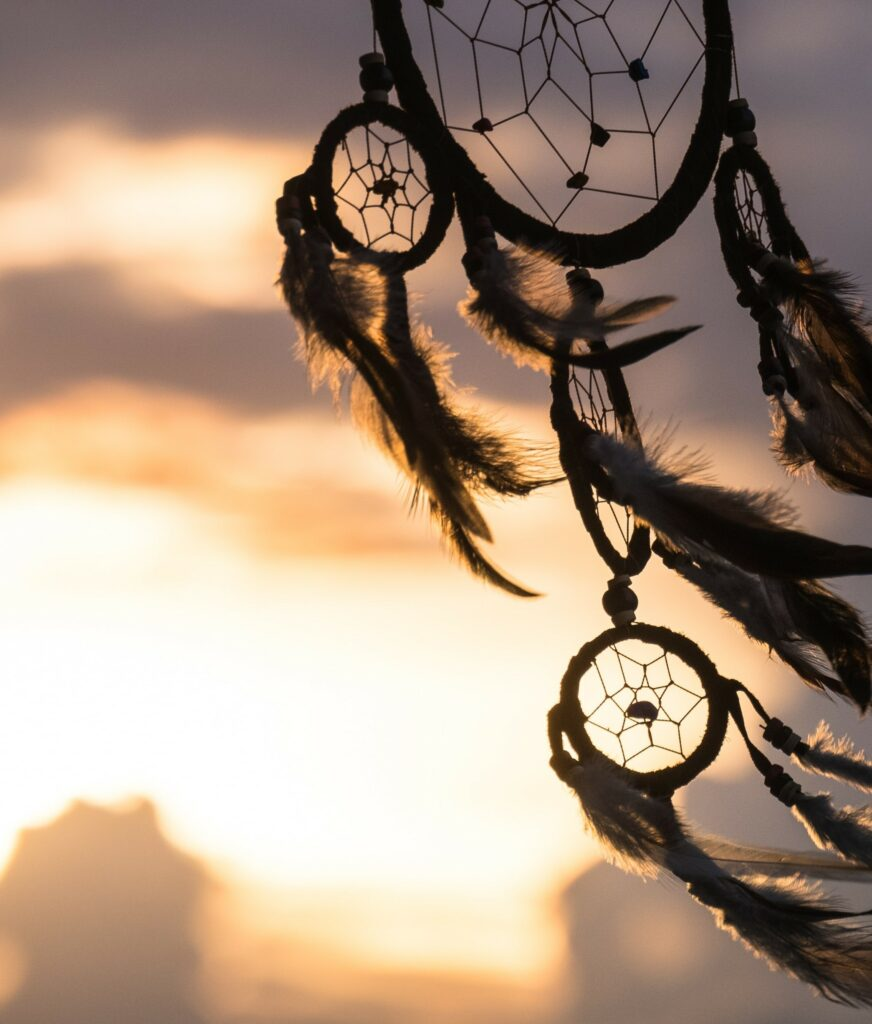 A dreamcatcher swaying in the wind in front of a sunset