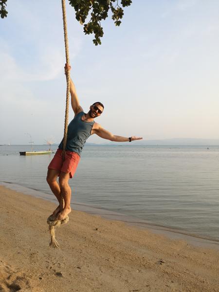 Man on rope swing on beach