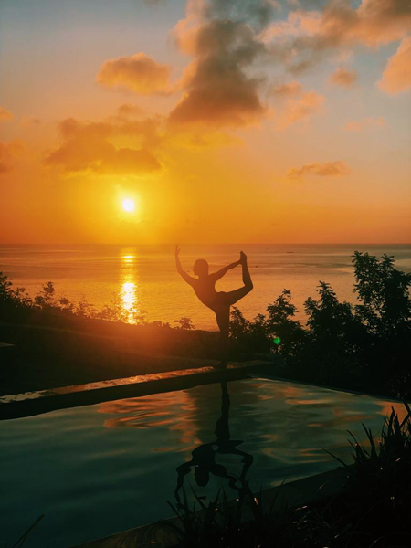 Woman doing pilates pose in sunset