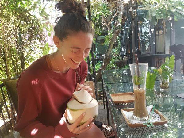 Woman laughing with coconut drink
