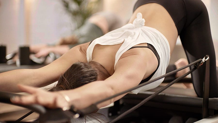 Woman stretching on Reformer bed