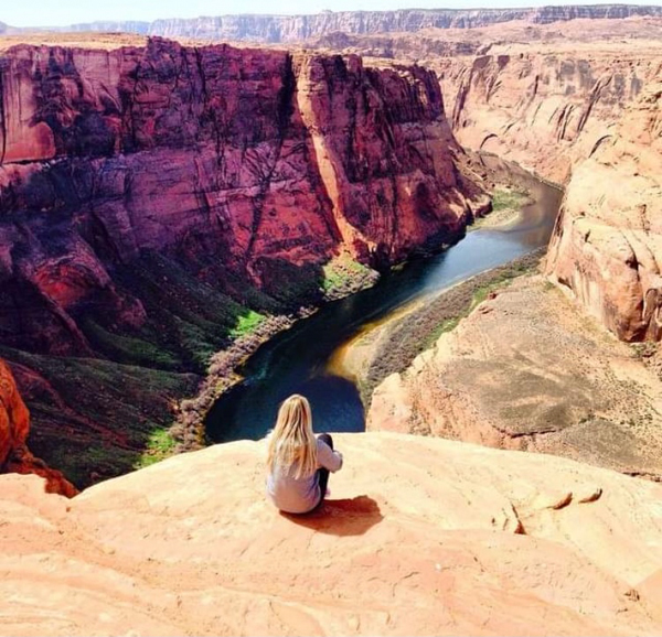 Woman sitting on edge of rock